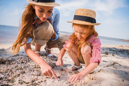 母と娘が貝殻を収集 写真素材