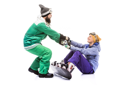 snowboarder helping girlfriend to get up Banco de Imagens