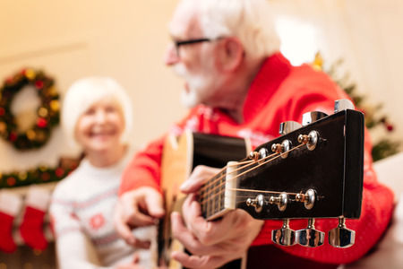 christmastime: senior couple playing on guitar