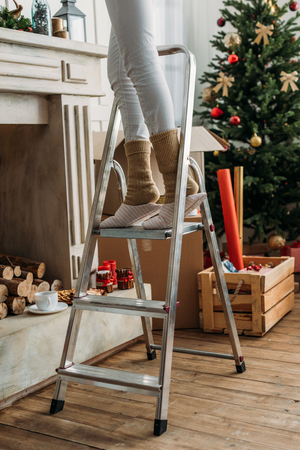 woman decorating room for christmas on stepladder