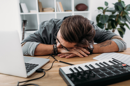 overworked musician sleeping at workplace