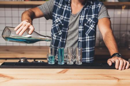 barman making alcohol shots