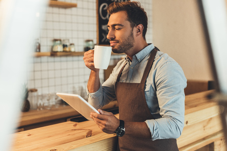 barista with cup of coffee using tablet