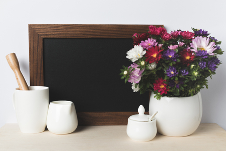 close-up view of blank board, kitchen utensils and beautiful flowers in vase on table