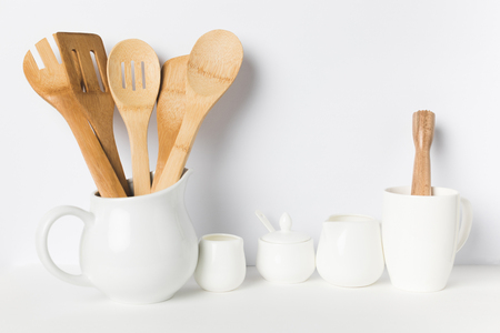 close-up view of wooden kitchen utensils in jug and ceramic cookware on table