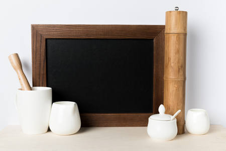 close-up view of blank board, bamboo container and kitchen utensils on table