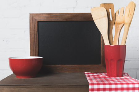 close-up view of wooden cooking utensils, bowl and blank board on table