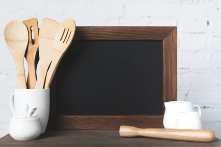 ceramic and wooden kitchen utensils and blank board on table