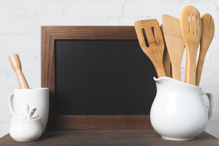 close-up view of ceramic and wooden kitchen utensils and blank board on table