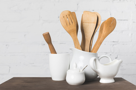 close-up view of wooden and ceramic kitchen utensils on table