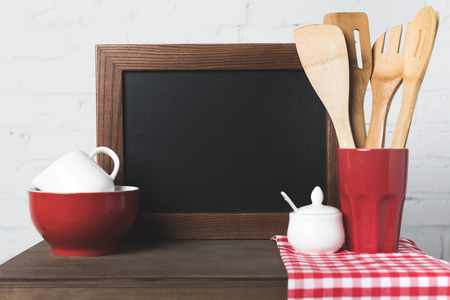 close-up view of wooden kitchen utensils, cookware and blank board on table