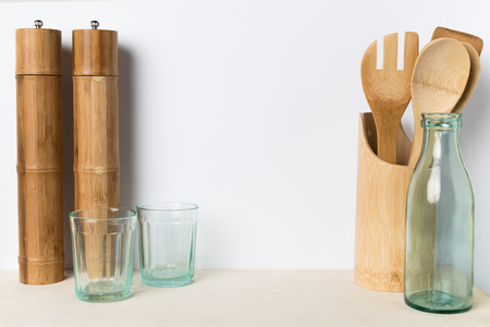close-up view of empty glasses, bottle, wooden utensils and bamboo containers in kitchen