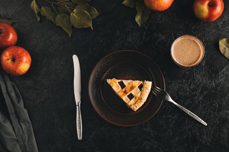 Vista superior del pedazo de pastel de manzana en un plato, cubiertos, vaso de cacao y manzanas frescas aisladas en superficie negra Foto de archivo - 88882294
