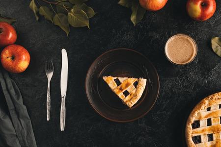 Vista superior de la pieza de pastel de manzana en un plato, cubiertos, vaso de cacao y manzanas frescas aisladas en superficie negra Foto de archivo - 88882297