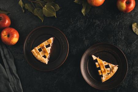 Vista superior de trozos de tarta de manzana casera en platos y manzanas frescas aisladas en tablero negro Foto de archivo - 88882304