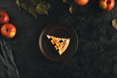 Vista superior do pedaço de torta de maçã no prato, maçãs e folhas isoladas na superfície preta Foto de archivo - 88882308