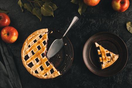 Lay Flat con tarta de manzana arreglada con servidor de pastel y manzanas frescas aisladas en superficie negra Foto de archivo - 88882307
