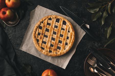 Vista superior de tarta de manzana casera, manzanas frescas y cubiertos aislados sobre mesa negro Foto de archivo - 88882356
