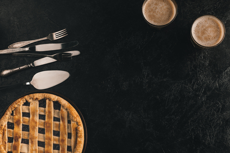 Apartamento leigos com torta caseira de baga, talheres e copos de cacau isolado na superfície preta Foto de archivo - 88882591