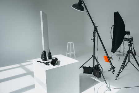 digital photo camera, lenses and light meter in photo studio with lighting equipment