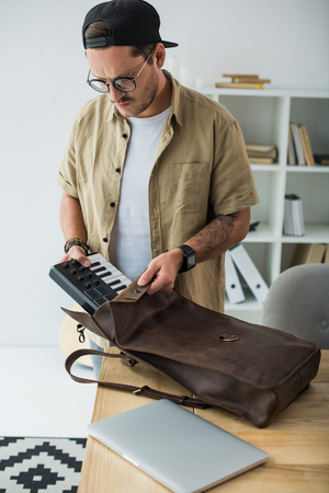 musician putting MPC pad into bag Stock Photo