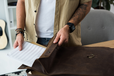 musician putting music notebook into bag Stock Photo
