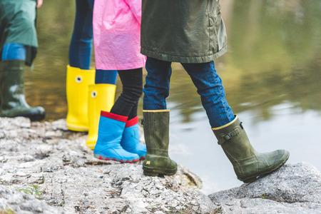 family in rubber boots standing on rock