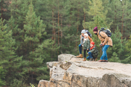family standing on rock in forest Stock Photo