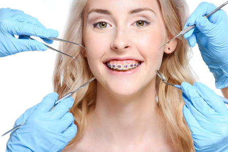 Hands holding dentist tools near woman Stock Photo