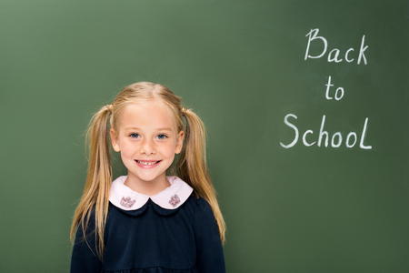happy schoolgirl next to chalkboard