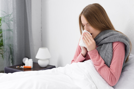 Sick girl wiping nose