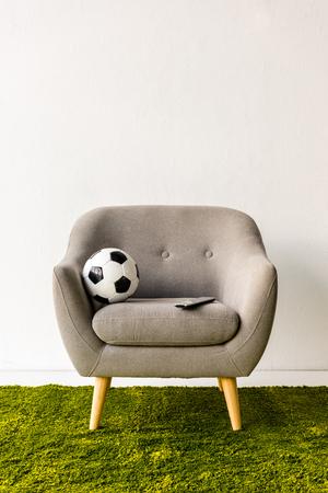 アームチェアにサッカーボールとリモコン 写真素材