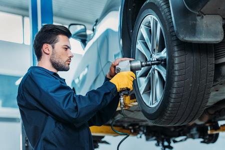Automechanic unscrewing tire bolts Stock Photo