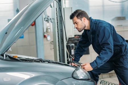 Automechanic patrząc pod maską samochodu