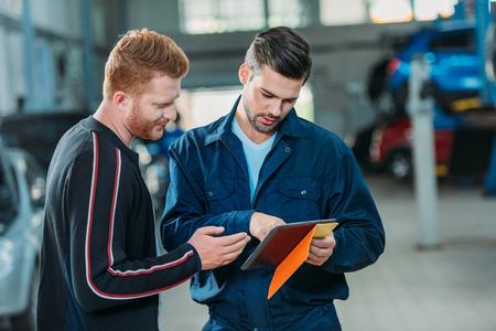 Automechaniker und Kunde, die digitale Tablette schauen