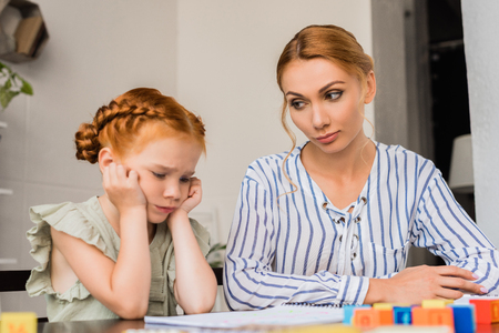 mother looking sceptical on sad daughter