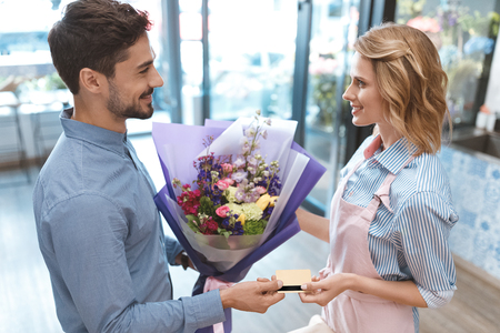 florist and client with credit card Imagens