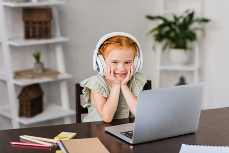 little girl with headphones and laptop
