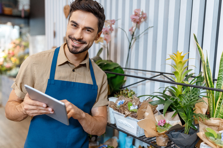 male florist with digital tablet