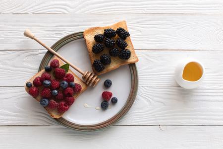 bovenaanzicht van ontbijt met verse bessen op toast en honing op houten tafelblad