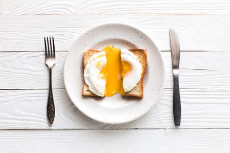 bovenaanzicht van ontbijt met gebakken ei op toast op plaat op houten tafelblad
