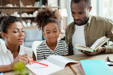 Mama en papa helpen dochter met huiswerk