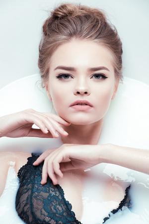 jonge vrouw met bad met melk Stockfoto