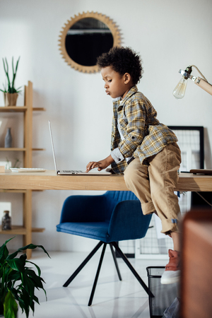 boy sitting on table and using laptop Stock Photo