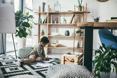 boy sitting on floor and drawing Stock Photo