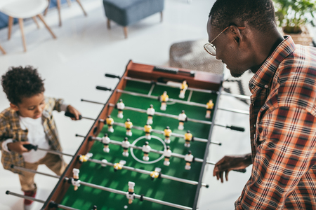 father and son playing playing foosball