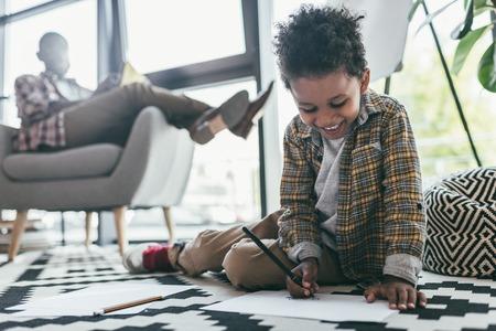 肘掛け椅子に座って父ながら描く少年 写真素材
