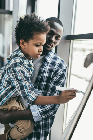 african-american father and son with whiteboard Stock Photo