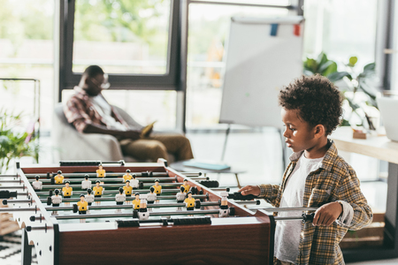 father and son playing playing foosball Stock Photo - 91367521