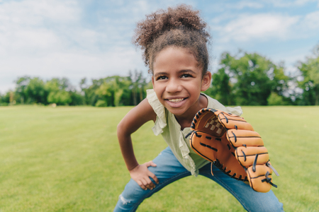 child playing baseball in park Stock Photo